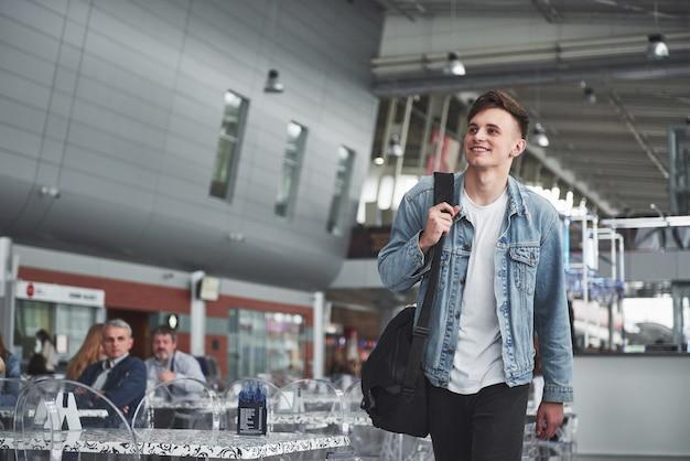 Молодой красавец с сумкой на плече спешит в аэропорт. Бесплатные Фотографии