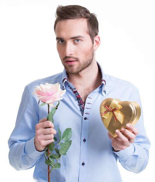 ピンクのバラと贈り物を持つ若いハンサムな男-白で隔離 無料写真