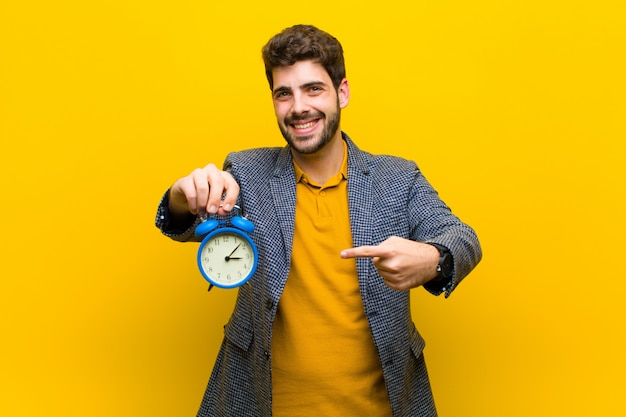 Young handsome man with an alarm clock  orange Premium Photo