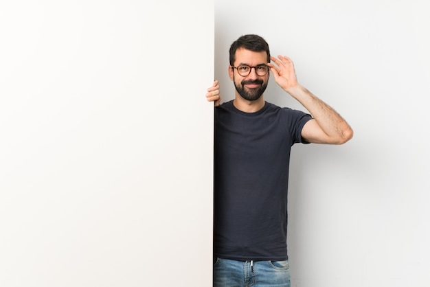 Young handsome man with beard holding a big empty placard with glasses and happy Premium Photo