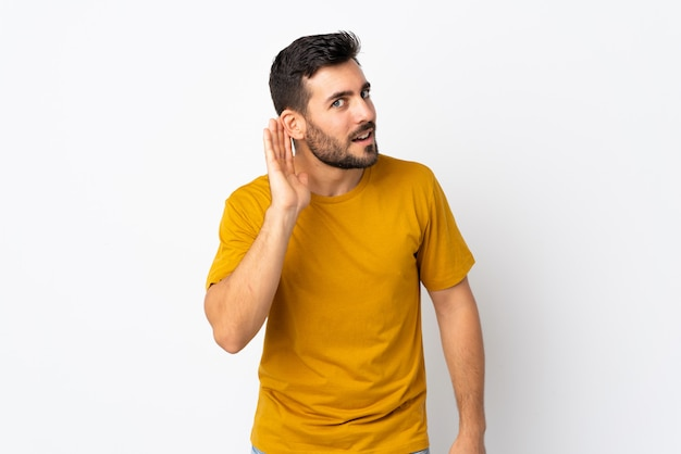 Молодой красивый мужчина с бородой, изолированные на белом, слушая что-то, положив руку на ухо Premium Фотографии