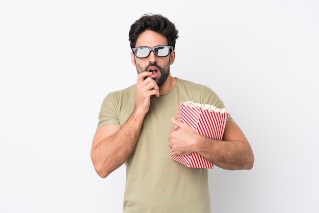Young handsome man with beard over isolated white wall with 3d glasses and holding a big bucket of popcorns Premium Photo