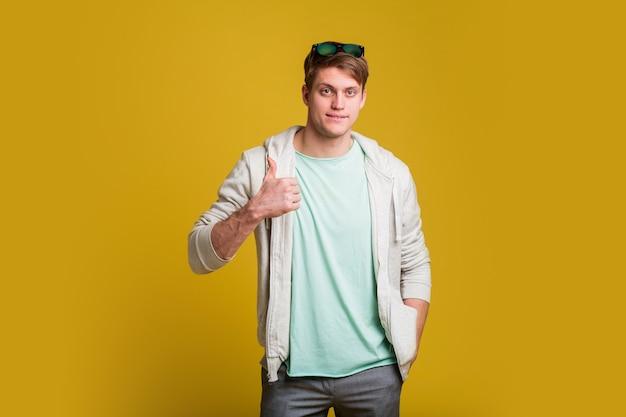 Giovane uomo bello con la barba in piedi sopra il muro giallo sorridente con la faccia felice guardando e indicando il lato con il pollice in su. Foto Gratuite