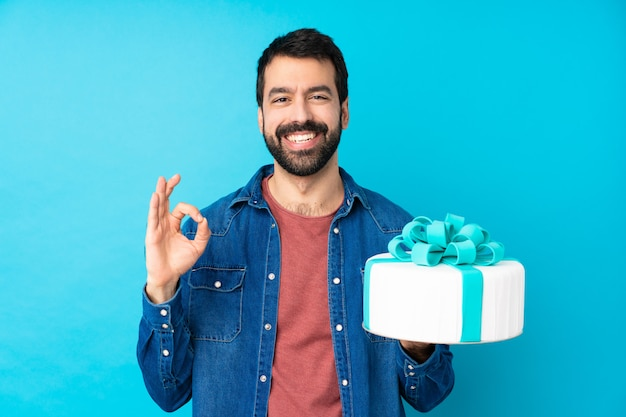 Young handsome man with a big cake over isolated blue wall showing an ok sign with fingers Premium Photo