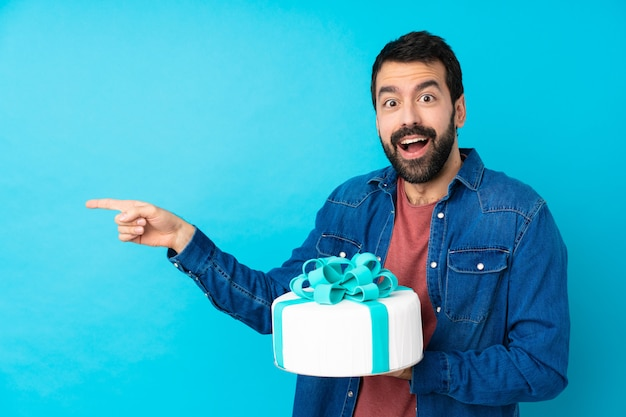 Young handsome man with a big cake surprised and pointing side Premium Photo