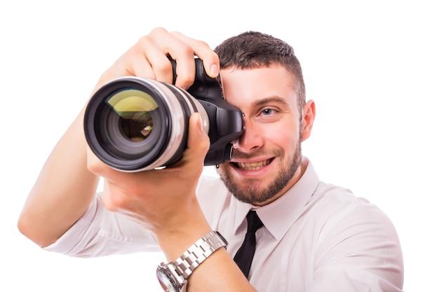 白い壁に隔離されたカメラを持つ若いハンサムな男。 無料写真