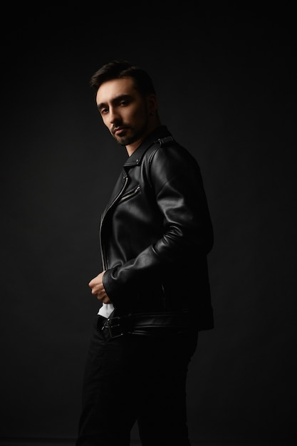 暗い背景でポーズをとって黒い革のジャケットで無精ひげを生やした顔を持つ若いハンサムな男 Premium写真