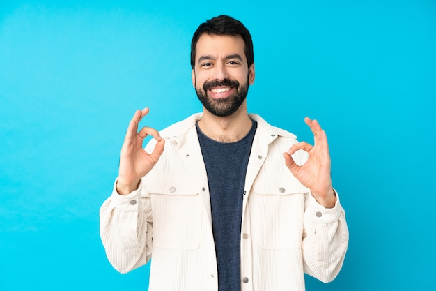 Young handsome man with white corduroy jacket over isolated blue wall showing an ok sign with fingers Premium Photo