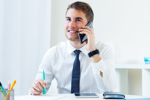 Young handsome man working in his office with mobile phone. Free Photo
