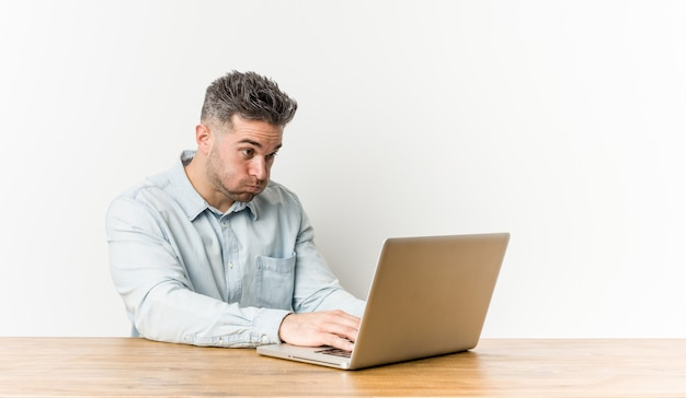 Young handsome man working with his laptop blows cheeks, has ti expression. facial expression . Premium Photo