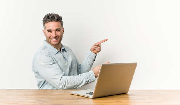 Young handsome man working with his laptop excited pointing with forefingers away. Premium Photo