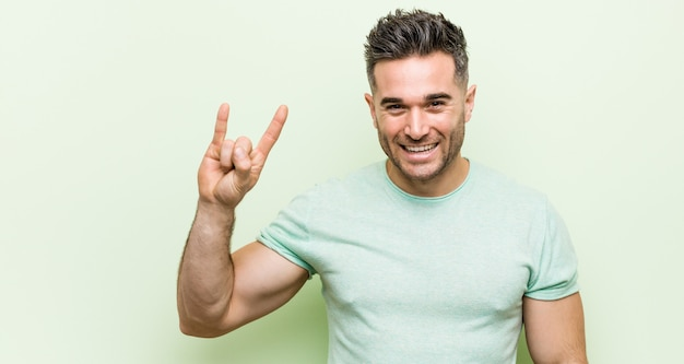 Young handsome manshowing a horns gesture as a revolution concept. Premium Photo