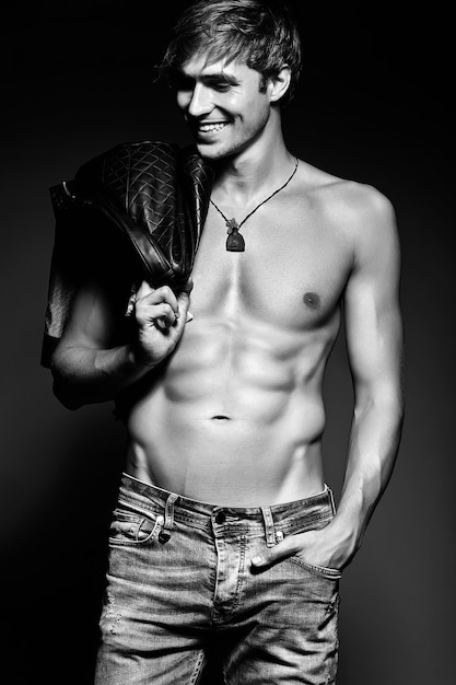 Young handsome muscled fit male model man posing in studio showing his abdominal muscles in  leather jacket Free Photo
