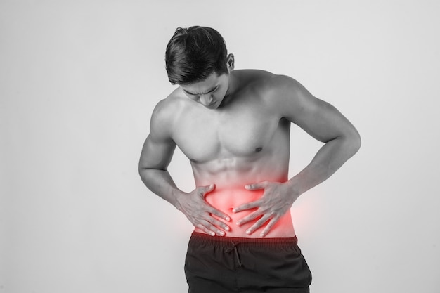 Young handsome muscular man has abdominal pain isolated on white background. Free Photo
