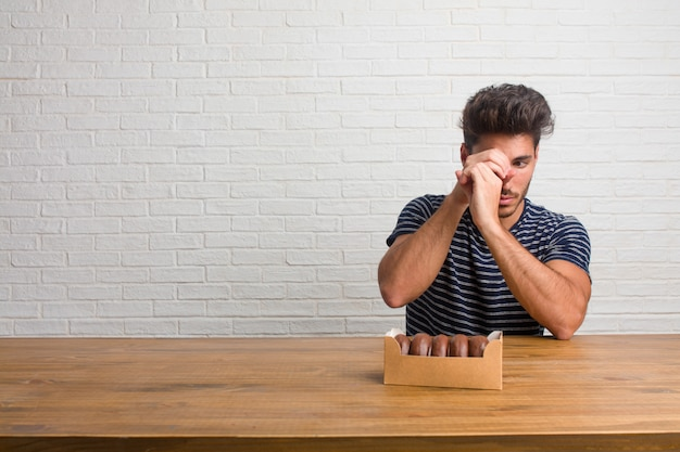 Young handsome and natural man sitting on a table looking through a gap Premium Photo