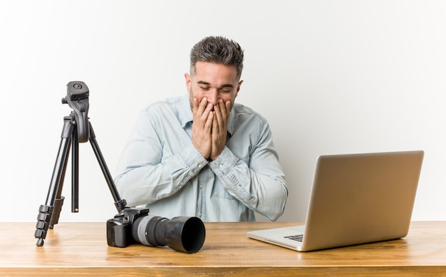 Young handsome photography teacher laughing about something, covering mouth with hands. Premium Photo