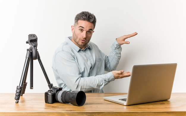 Young handsome photography teacher shocked and amazed holding a copy space between hands. Premium Photo