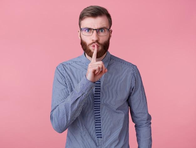 眼鏡と縞模様のシャツを着た若いハンサムな赤いひげを生やした男は、唇に指を保ち、秘密の情報を伝え、ピンクの背景に分離されたハッシュジェスチャーを示しています。 無料写真