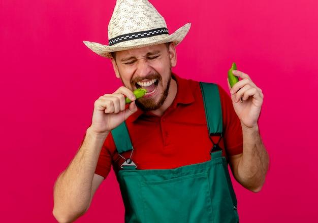 Giovane giardiniere slavo bello in uniforme e cappello che tiene e pepe mordace con gli occhi chiusi Foto Gratuite