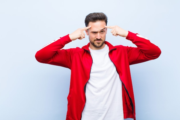 Young handsome sports man or monitor with a serious and concentrated look, brainstorming and thinking about a challenging problem against flat wall Premium Photo