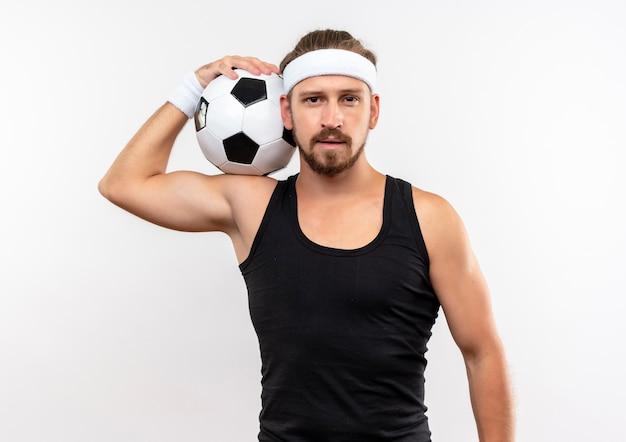 Молодой красивый спортивный мужчина с головной повязкой и браслетами, держащий футбольный мяч на плече, выглядит изолированным на белом пространстве Бесплатные Фотографии