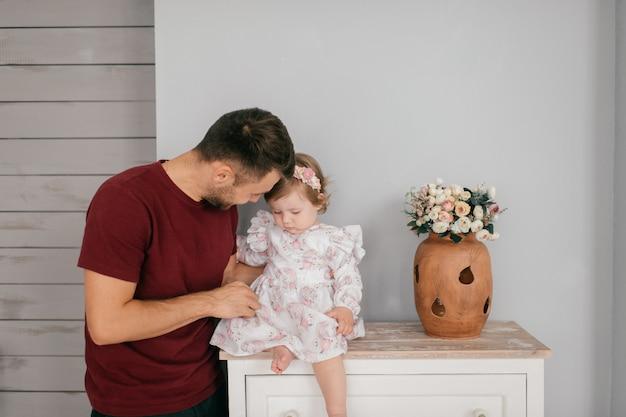 明るい部屋で若いハンサムな強いお父さんは彼のかわいい小さな娘を保持します Premium写真