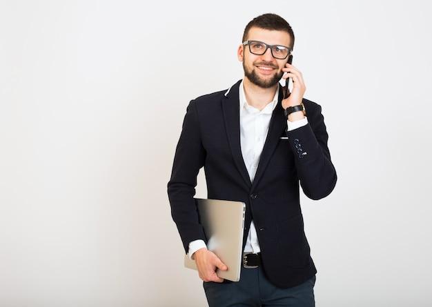 Giovane uomo bello alla moda hipster in giacca nera, stile di affari, camicia bianca, isolato, sfondo bianco, sorridente, attraente, guardando fiducioso, tenendo il laptop, parlando sullo smartphone Foto Gratuite