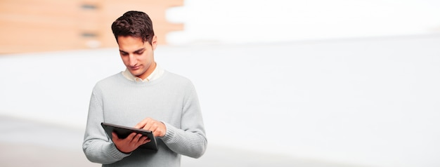 Young handsome tanned man with a touch screen tablet Premium Photo
