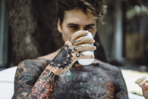Young handsome tattooed man having breakfast in bed in the open air outdoors in the garden Free Photo