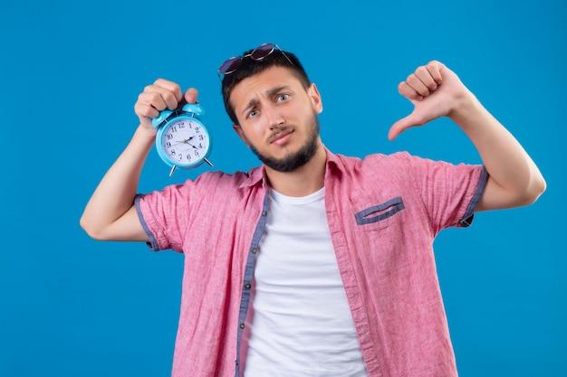 Молодой красивый путешественник, держащий будильник, смотрит в камеру с грустным выражением лица и показывает палец вниз, стоя на синем фоне Бесплатные Фотографии