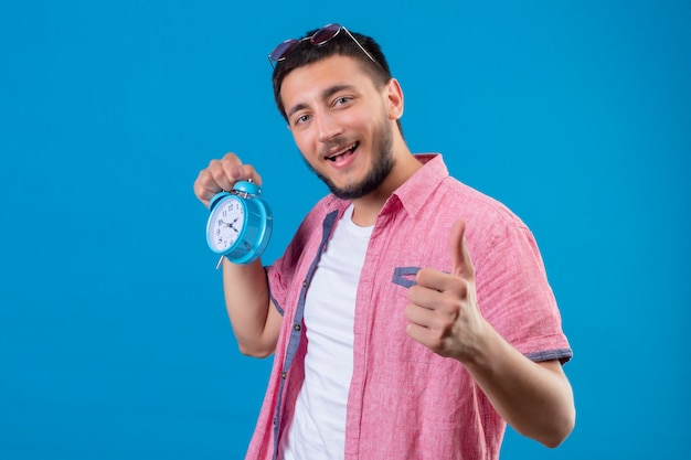 Young handsome traveler guy holding alarm clock looking positive and happy smiling showing thumbs up standing over blue background Free Photo