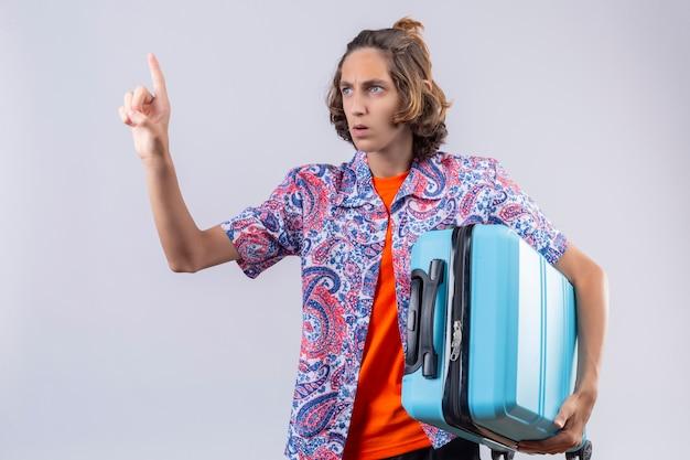 スーツケースジェスチャーを保持している若いハンサムな旅行者の男は立っている顔に深刻な自信を持って式で1分待ちます 無料写真