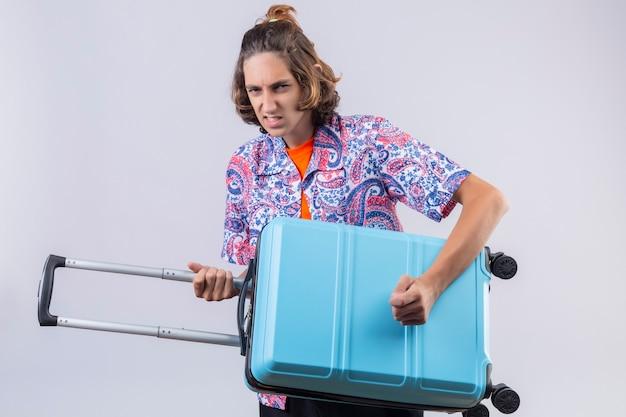 Молодой красивый путешественник, держащий чемодан в качестве гитары, смотрит с сердитым выражением лица на белом фоне Бесплатные Фотографии