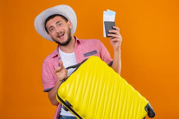 Молодой красивый путешественник в летней шляпе держит чемодан и авиабилеты, глядя в камеру, выходит и счастливо улыбается, готовый к путешествию, стоя на оранжевом фоне Бесплатные Фотографии