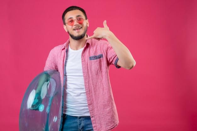 ピンクの背景の上に立って私をジェスチャーと呼んでいる陽気な笑みを浮かべてカメラを見てインフレータブルリングを保持しているサングラスを着ている若いハンサムな旅行者男 無料写真