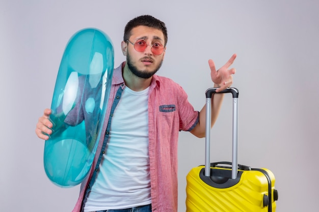 Young handsome traveler guy wearing sunglasses holding inflatable ring looking at camera with confuse expression on face standing with travel suitcase over white background Free Photo