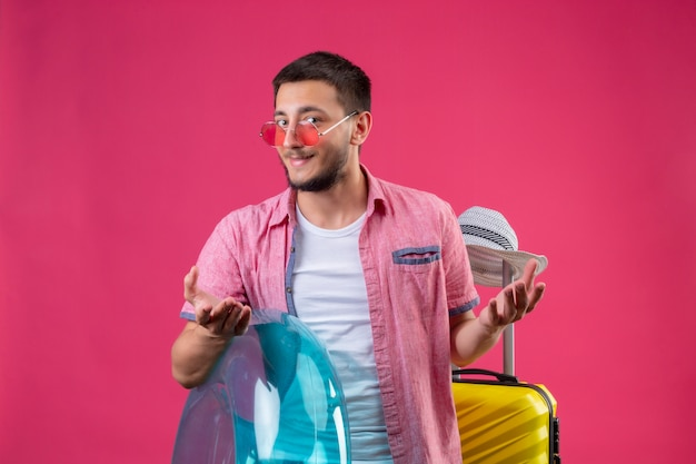 Occhiali da sole d'uso del giovane tipo bello del viaggiatore che tengono anello gonfiabile che sta con la valigia di viaggio che esamina macchina fotografica che sorride sleale con le armi alzate sopra fondo rosa Foto Gratuite