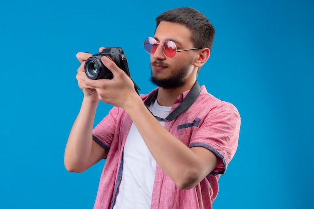 Young handsome traveler guy wearing sunglasses taking a picture with camera standing over blue background Free Photo