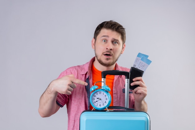 Young handsome traveler man holding blue suitcase and airplane tickets with alarm clock confused and disappointed standing over white wall Free Photo