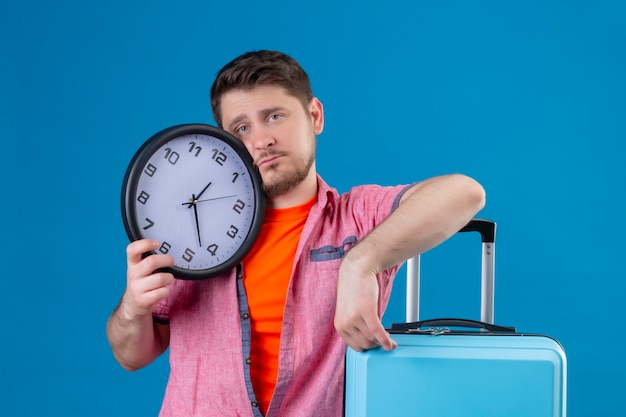Young handsome traveler man holding suitcase and clock with sad expression Free Photo