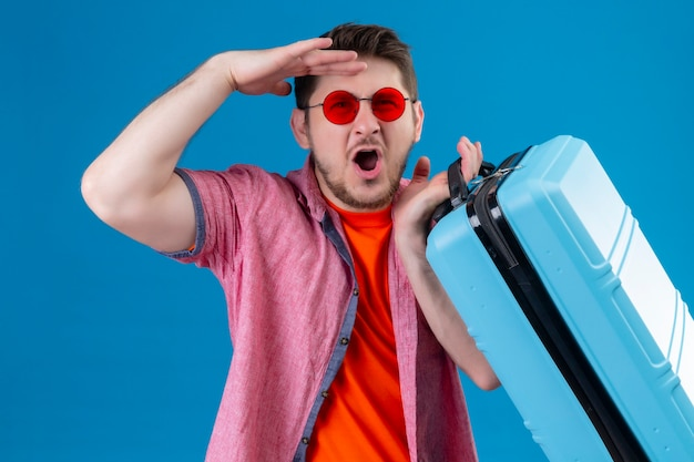 Young handsome traveler man wearing sunglasses holding suitcase looking surprised and amazed standing over blue wall Free Photo