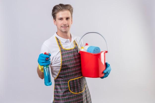 クリーニングツールでバケツを保持している自信を持って笑顔でスプレーを洗浄エプロンとゴム手袋を着用して若いhansdome男 無料写真
