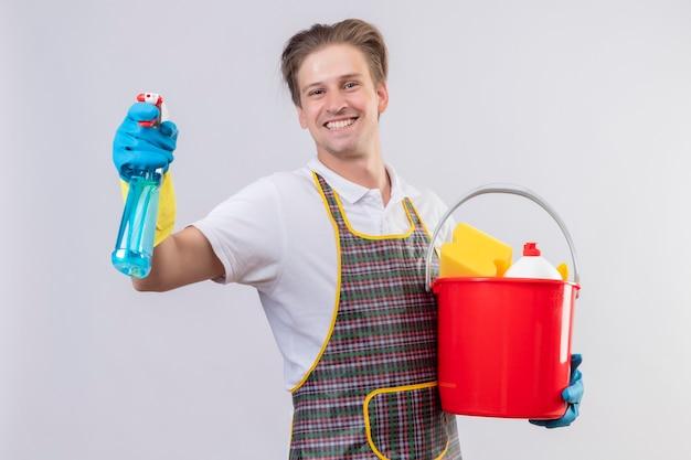 クリーニングツールとスプレーを洗浄するバケットを保持しているエプロンとゴム手袋を着用して若いhansdome男 無料写真