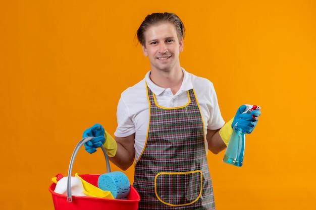 掃除道具とバケツを保持しているエプロンとゴム手袋を着用して若いhansdome男 無料写真