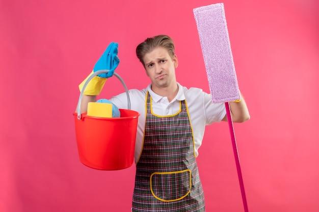 Grembiule da portare del giovane hansdome e guanti di gomma che tengono secchio con strumenti di pulizia e mop Foto Gratuite