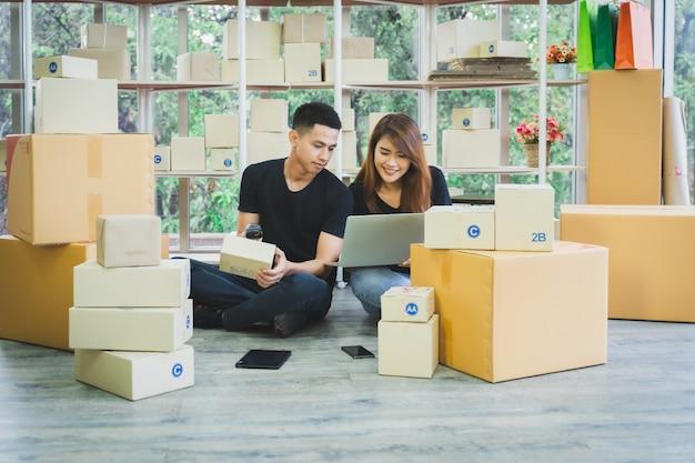 Молодая счастливая азиатская деловая пара работает вместе, используя ноутбук и сканер штрих-кода с упаковкой посылочной коробки в их домашнем офисе, онлайн-продавце мсп и концепции доставки Premium Фотографии