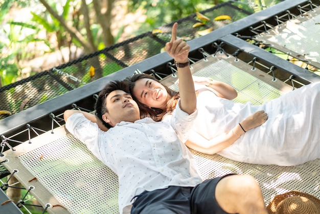Young happy asian couple in love on cradle balcony Premium Photo