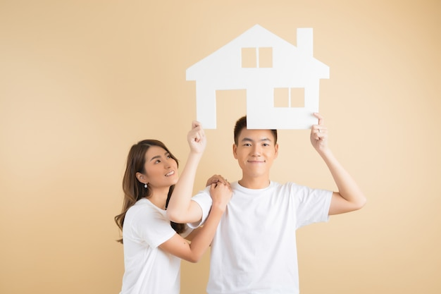 Young happy asian couple presenting the symbols of house Free Photo