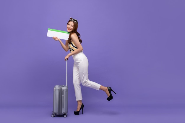 荷物と飛行機のチケットを持つ若い幸せなアジア女性観光客 Premium写真