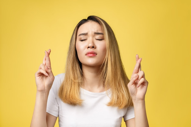 Young Happy Asian Woman With Fingers Crossed On Yellow